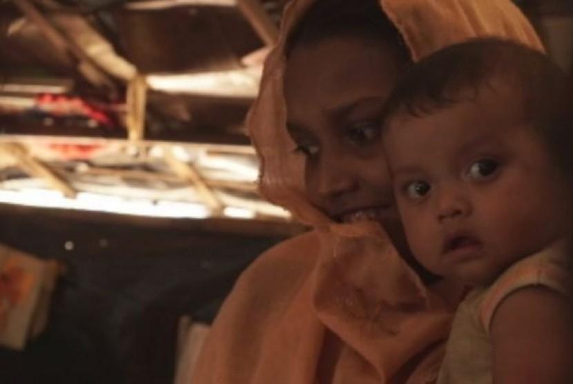 Noor Fatima, seorang pengungsi Rohingya yang melarikan diri ke Bangladesh dari Myanmar, dengan 1 dari 4 anaknya.
