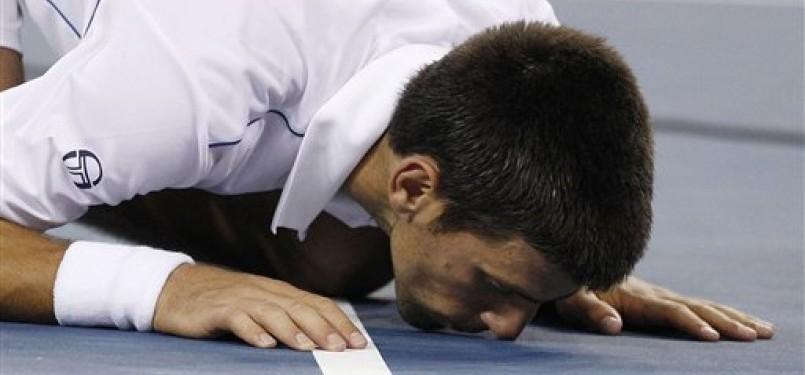 Novak Djokovic mencium lapangan usai memastikan juara Amerika Terbuka dengan mengalahkan Rafael Nadal di partai final.