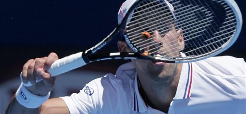Novak Djokovic, petenis asal Serbia, melepaskan pukulan forehand saat menghadapi petenis Italia, Paolo Lorenzi, di putaran pertama turnamen Australia Terbuka di Melbourne, Australia, Selasa (17/1).