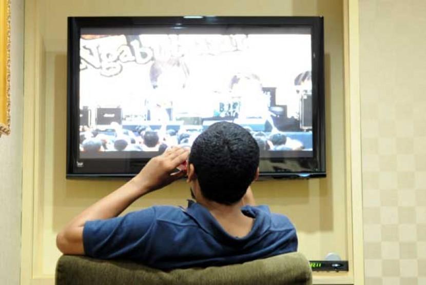 Orang duduk menonton TV. (ilustrasi)