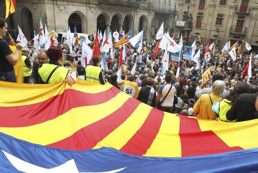 Orang-orang membentangkan bendera pro-kemerdekaan Katalunya dalam sebuah demonstrasi di Santiago de Compostela, Provinsi Galicia, Spanyol, Sabtu (30/9). Katalunya mengadakan referendum kemerdekaan pada Ahad (1/10), meski telah dilarang oleh Mahkamah Konstitusi Spanyol.