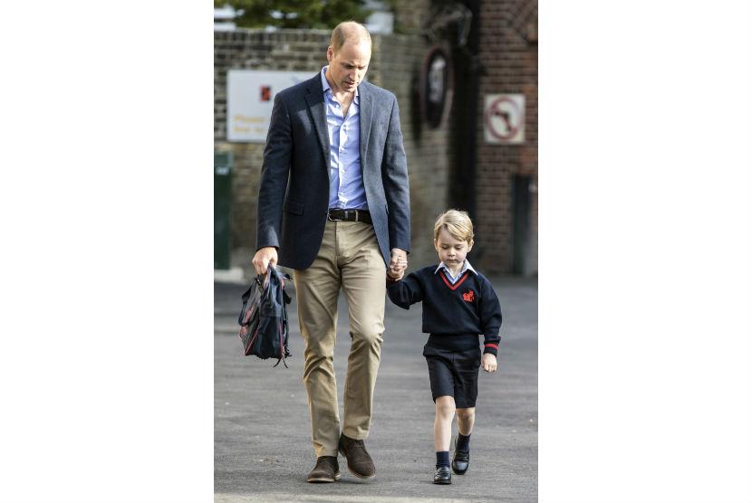 Pangeran William menggandeng tangan putranya Pangeran George di hari pertama sekolah, Kamis (7/9).