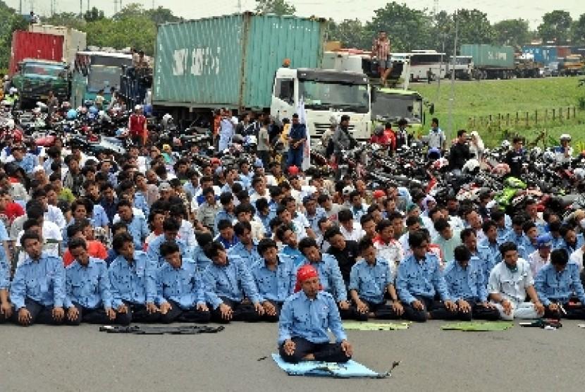 Para buruh melakukan Shalat Jumat saat aksi blokir jalan tol Jakarta-Cikampek, Cibitung, Jawa Barat (ilustrasi).