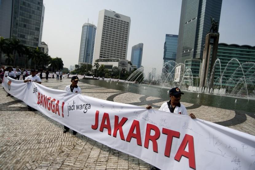 Para panitia pengawas lapangan (PPL) Panwaslu memegang spanduk Bangga Jakarta dalam aksi simpati Panwaslu untuk DKI Jakarta Pemilu Damai di Bundaran HI, Jakarta, Ahad (7/10).