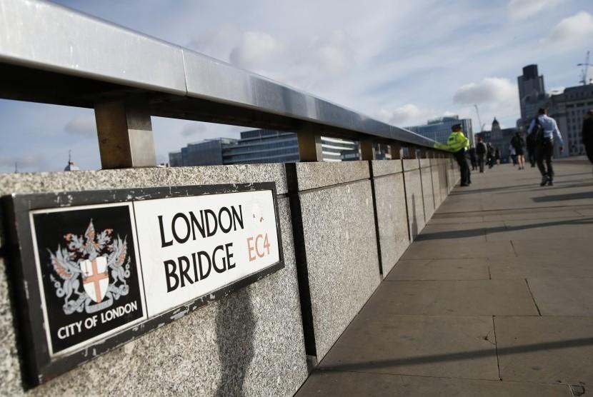 Para pejalan kaki melewati seorang polisi di London Bridge, London, Senin (5/6). Polisi menahan beberapa orang dan melakukan penyelidikan setelah rangkaian serangan diduga sebagai aksi terorisme menewaskan beberapa orang dan melukai lebih dari 40 lainnya di jantung kota London.