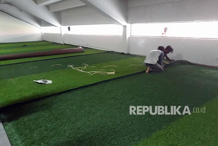 Para pekerja sedang menyelesaikan renovasi stadion Gelora Sriwijaya di komplek Jakabaring Sport City (JSC), diantaranya dengan pemasangan rumput sintetis tempat pemanasan di depan ruang ganti  yang akan digunakan untuk cabang sepakbola Asian Games XVIII-2018.