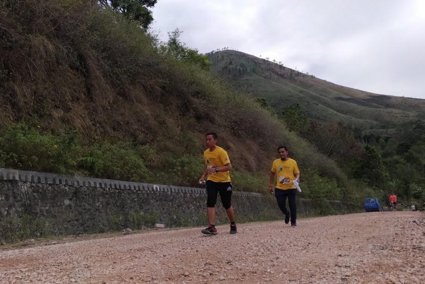 Para pelari Samosir Lake Toba Ultra Marathon sedang melintasi kawasan wisata Danau Toba, Sumatera Utara.