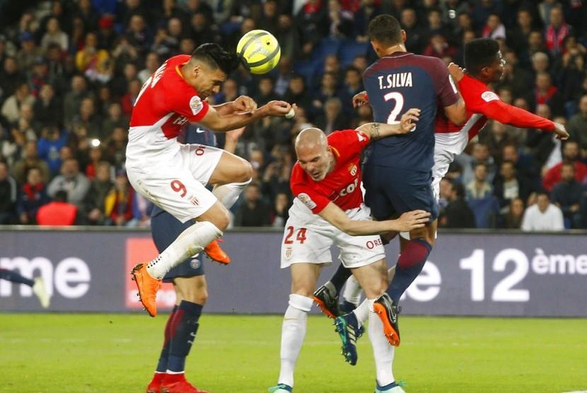 Para pemain AS Monaco (baju putih merah) jatuh bangun mengadang serangan Paris Saint-Germain.