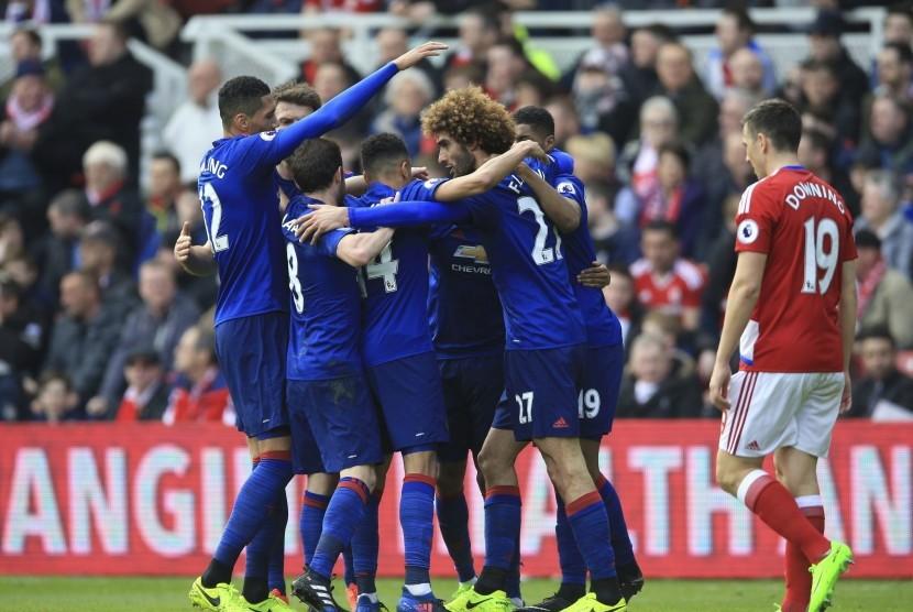 Para pemain Manchester United merayakan gol Marouane Fellaini (kanan tengah) pada laga Liga Primer Inggris lawan Middlesbrough di stadion Riverside, Ahad (19/3). United menang 3-1.