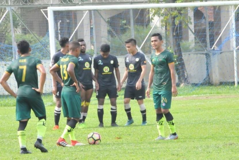 Para pemain PS Tira (kostum hijau-hijau) bersiap mengeksekusi tendangan bebas pada laga persahabatan kontra Barito Putera di Lapangan BAIS TNI, Bogor, Kamis (22/2).