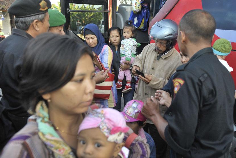 Anggota Satuan Polisi Pamong Praja memeriksa identitas pemudik saat operasi penertiban pendatang pada arus balik Idul Fitri 1435 H di Terminal Ubung, Denpasar, Sabtu (2/8). (Antara/Nyoman Budhiana)
