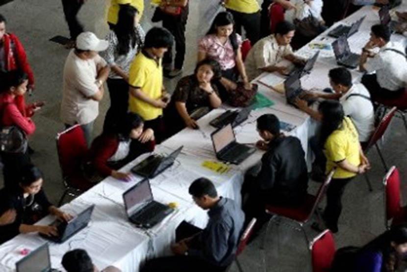 Para pencari kerja melihat informasi lowongan kerja pada sebuah bursa kerja.