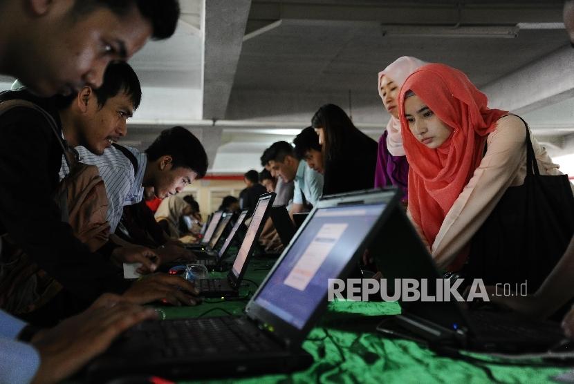 Para pencari kerja mengisi formulir saat menghadiri pelaksanaan Bursa Kerja di Jakarta, Jumat (22/4). (Republika/Tahta Aidilla)