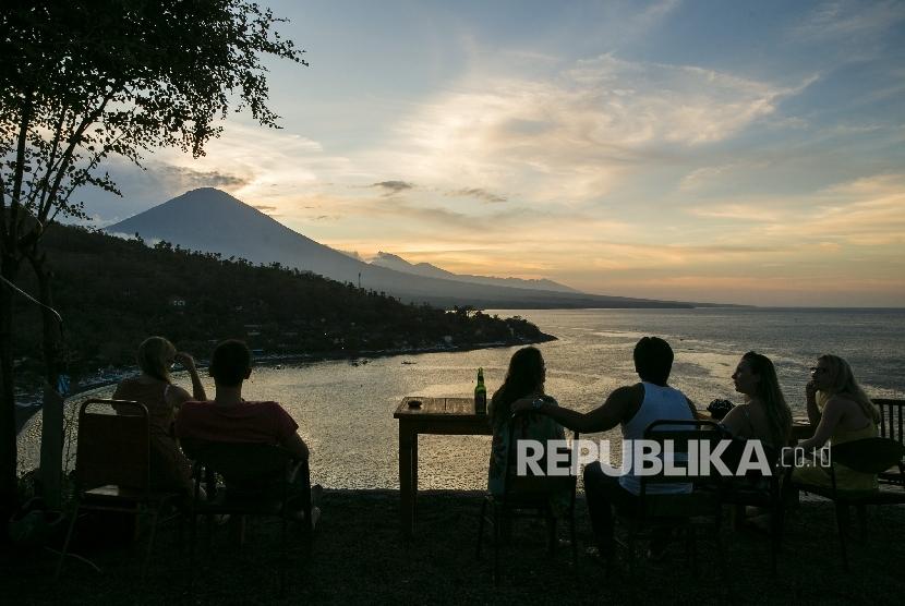 Para wisatawan menyaksikan matahari terbenam di atas Gunung Agung dari desa Amed di Karangasem, Bali, Indonesia (10/10).