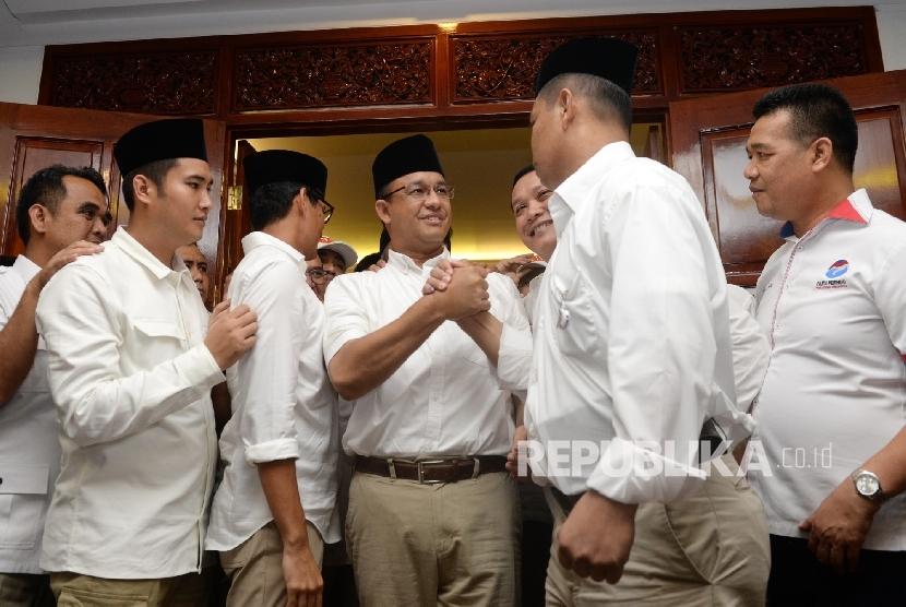 Pasangan Cagub Cawagub DKI Jakarta Anies Baswedan dan Sandiaga Uno menerima ucapan selamat dari simpatisan usai menggelar konferensi pers di Posko Pemenangan Paslon Anies-Sandi Kertajaya, Jakarta, Rabu (19/4).