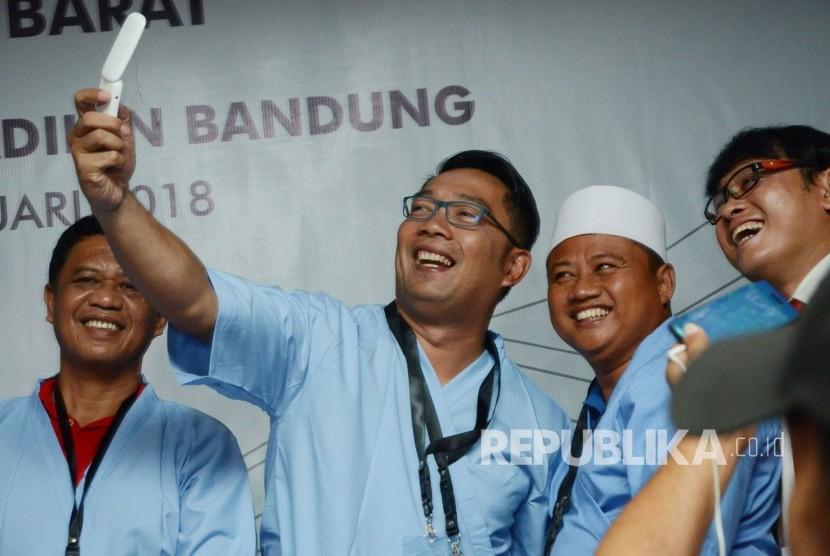 Pasangan Calon Gubernur dan Wakil Gubernur Jawa Barat Ridwan Kamil dan Uu Ruzhanul Ulum berswafoto usai melakukan pemeriksaan kesehatan di RS Hasan Sadikin, Kota Bandung, Kamis (11/1).