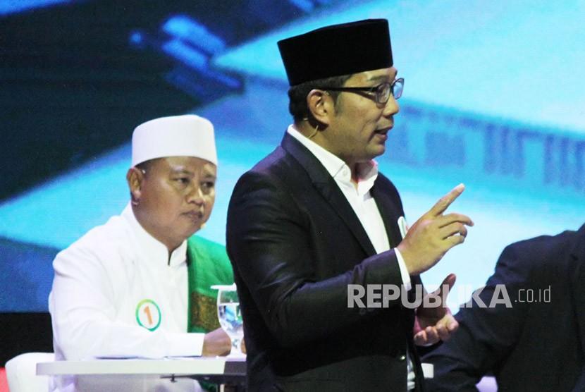 Pasangan Ridwan Kamil dan Uu Ruzhanul Ulum menyampaikan paparannya saat Debat Publik Pertama Pilgub Jawa Barat 2018 bersama empat pasangan calon gubernur dan wakil gubernur Jawa Barat, di Gedung Sabuga, Kota Bandung, Senin (12/3).