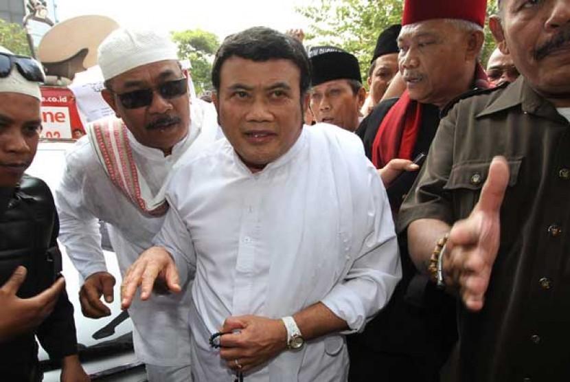 Pedangdut Rhoma Irama (tengah) dikawal pendukungnya ketika memenuhi panggilan Panwaslu DKI Jakarta, Jakarta Pusat, Senin (6/8).