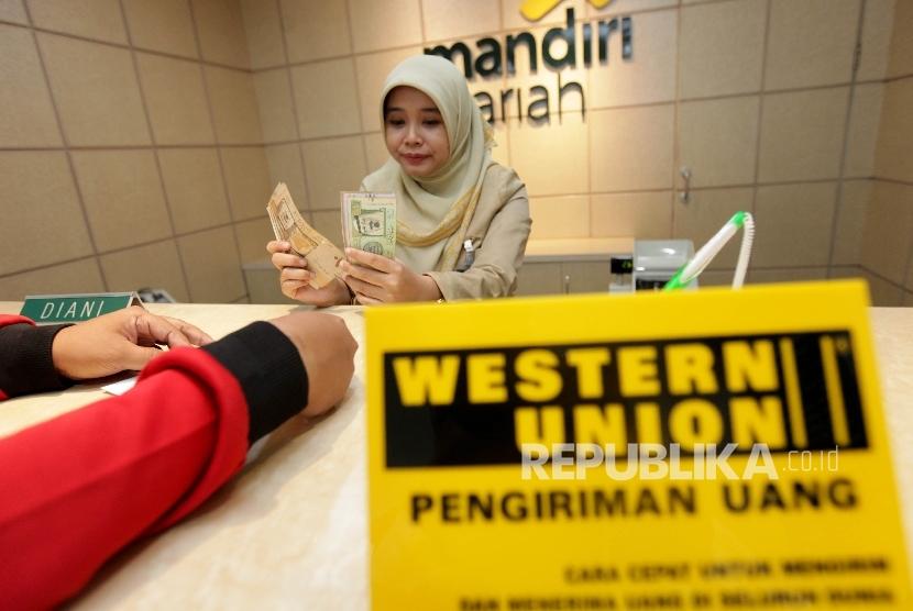 Pegawai Mandiri Syariah tengah melayani nasabah yang melakukan transfer dana ke luar negeri di Bank Mandiri Syariah Cabang Menteng, Jakarta, Selasa (12/9).