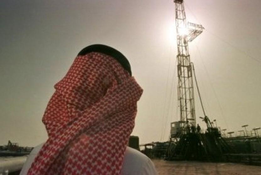 Pejabat perusahaan minyak Arab Saudi, Aramco, tengah memeriksa sebuah pengeboran minyak di Arab Saudi.