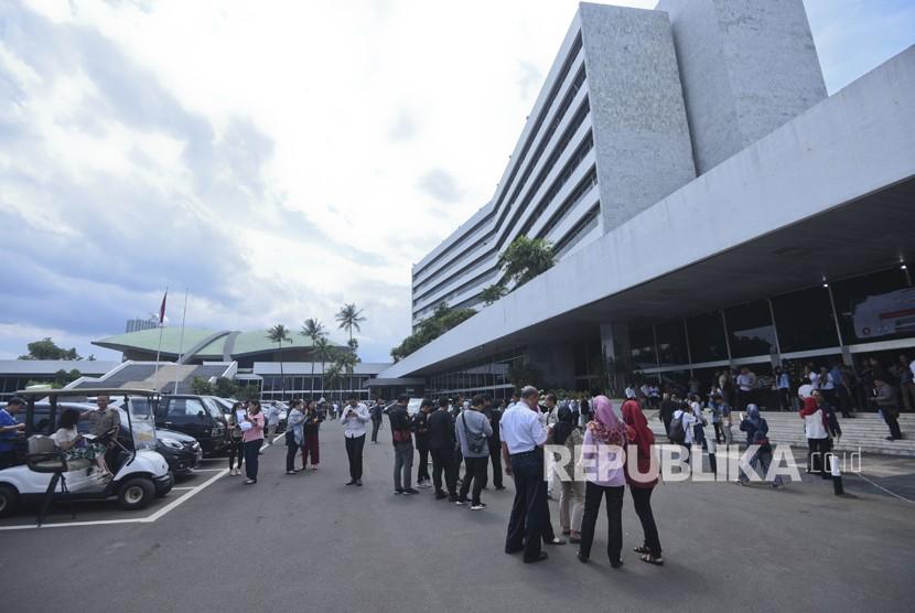 Pekerja berhamburan keluar Gedung Nusantara III saat merasakan gempa di Kompleks Parlemen, Senayan, Jakarta, Selasa (23/1).