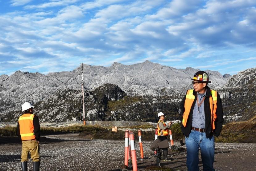 Pekerja melintas berlatarbelakang pegunungan Jayawijaya di kawasan Grasberg Mine milik PT. Freeport Indonesia (PTFI ) di Tembagapura, Mimika, Timika, Papua, Minggu (15/2).