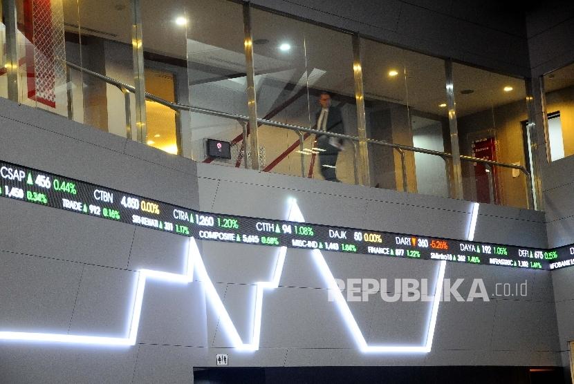 Pekerja melintas disamping layar pergerakan Indeks Harga Saham Gabungan (IHSG), Gedung Bursa Efek Indonesia (BEI) Jakarta, Selasa (18/4).