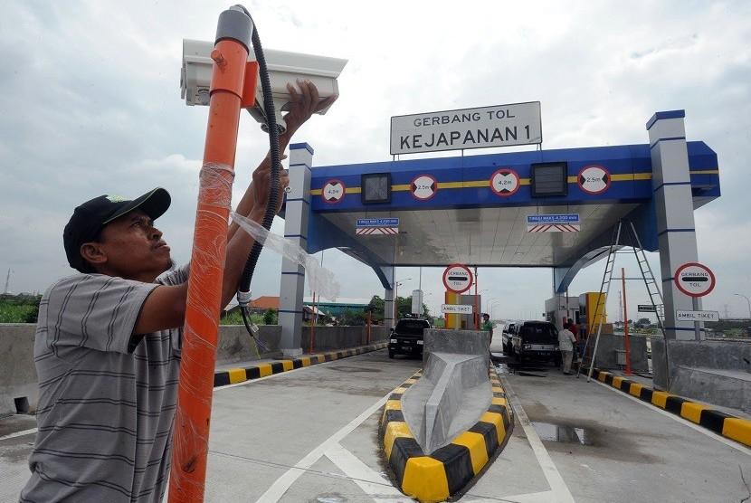 Pekerja memasang CCTV di depan pintu gerbang tol Gempol-Pandaan, di Kejapanan, Pasuruan, Jawa Timur, Jumat (13/2).