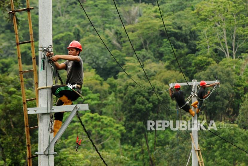 Pekerja memasang instalasi listrik di desa Kamiri, Barru, Sulawesi Selatan, Senin (15/1).