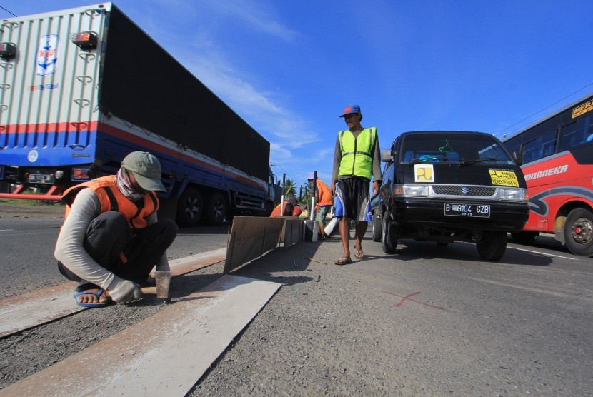 Pekerja membuat penutup putaran arah (U-turn) di Jalur Pantura Lohbener, Indramayu, Jawa Barat, Jumat (16/6).