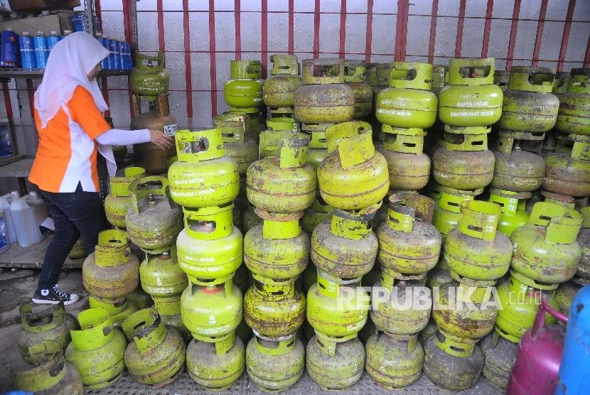 Pekerja memeriksa tabung gas tiga kilo di tempat penjualan gas di Jakarta, Ahad (2/4).