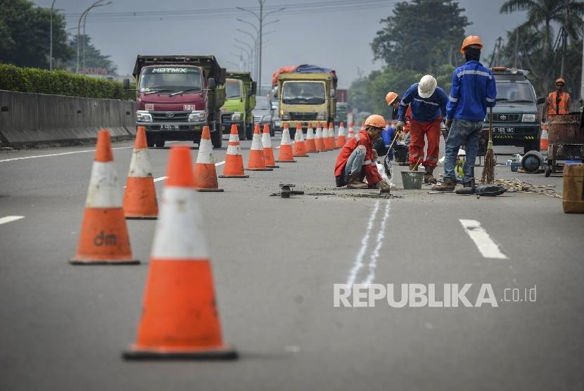 Pekerja memperbaiki jalan yang rusak di jalan tol Tangerang-Merak Kawasan Balaraja, Banten, Ahad (4/6).