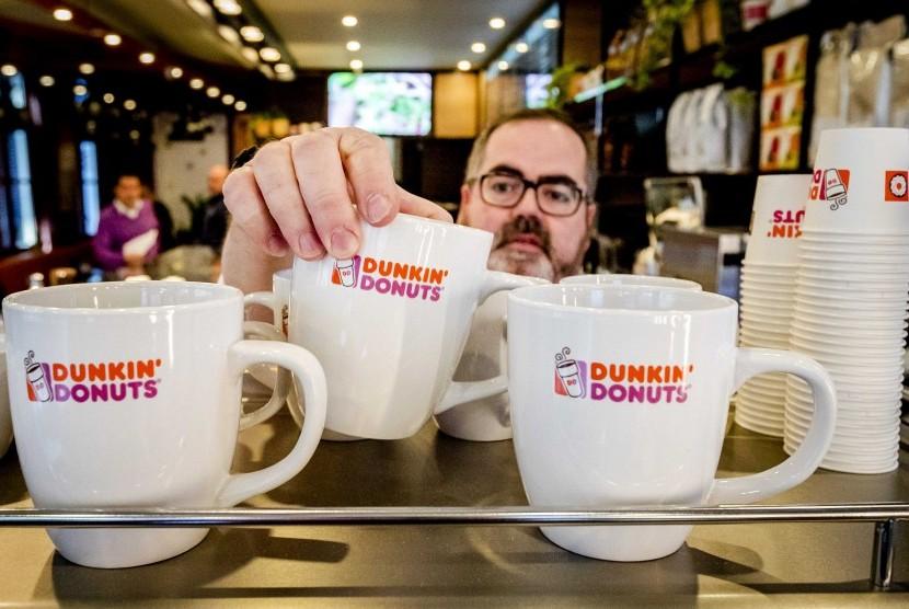 Pekerja menata cangkir minum di gerai Dunkin Donuts.
