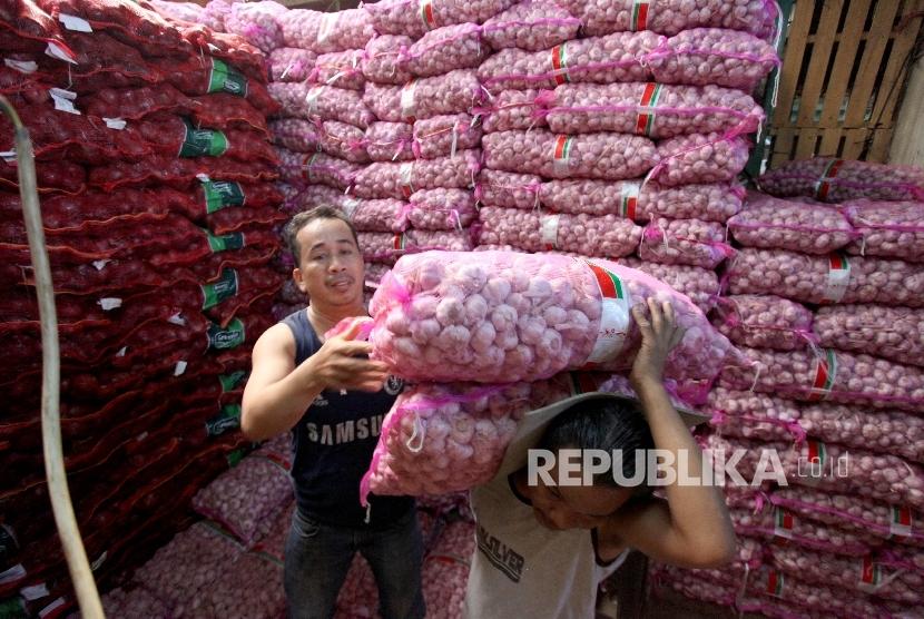 Pekerja mengangkut bawang putih di Pasar Induk Kramat Jati, Jakarta, Rabu (17/5).