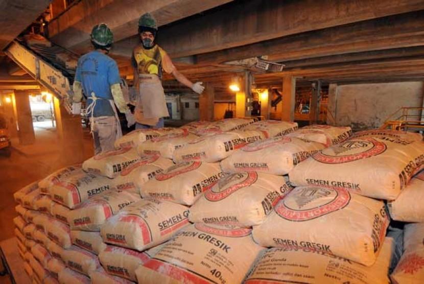 Pekerja mengemas semen ke dalam karung di pabrik semen milik PT Semen Indonesia (Persero) Tbk.