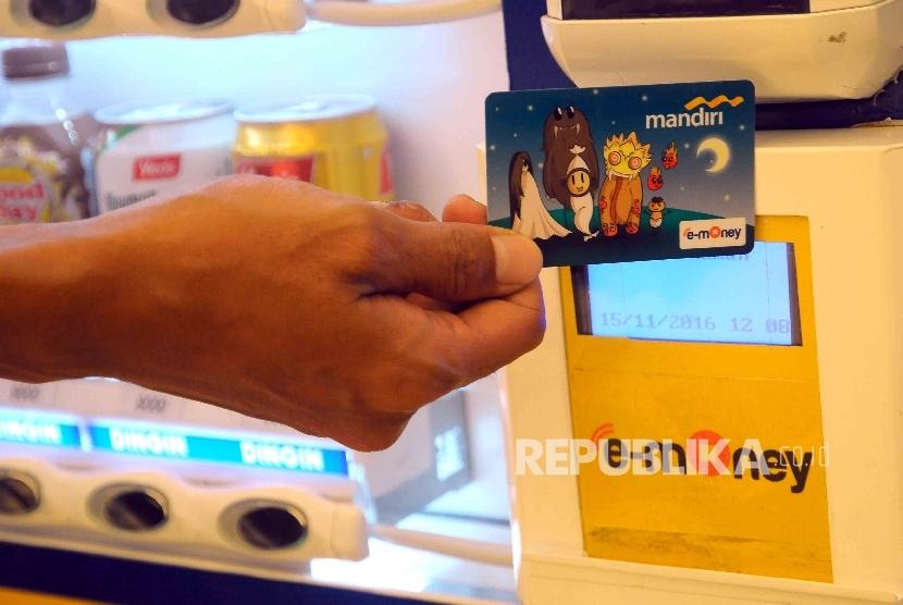 Pekerja menggunakan kartu uang elektronik (e-money) melakukan transaksi pembelian di salah satu bank di Jakarta, Senin (21/11).