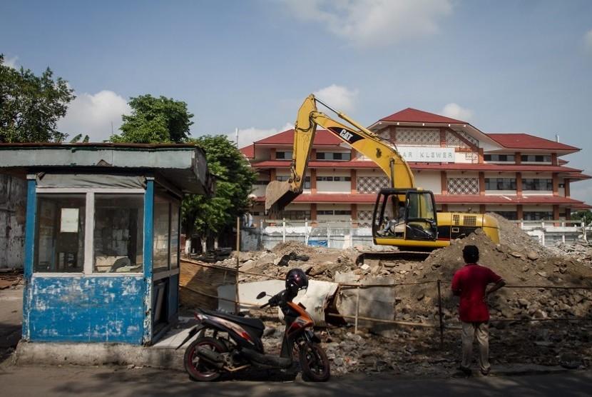 Pekerja mengoperasikan alat berat membongkar bangunan Pasar Klewer sisi timur, Solo, Jawa Tengah, Senin (4/12).