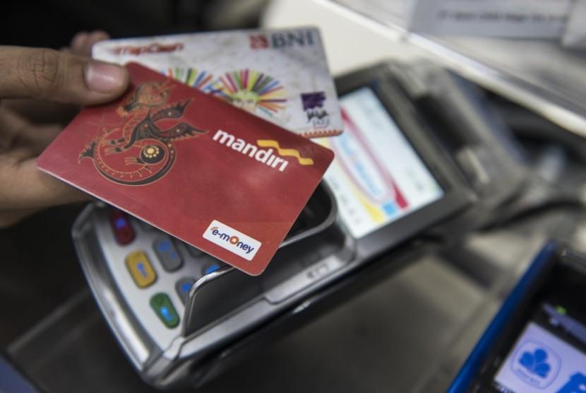 Pekerja menunjukan kartu uang elektronik sebelum isi ulang (top-up) di Bandung, Jawa Barat, Selasa (19/9).