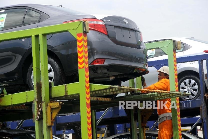 Pekerja menurunkan mobil Toyota dari truk penganagkut yang akan di ekspor di Tanjung Priok Car Terminal (TPT), Jakarta, Rabu (8/3).