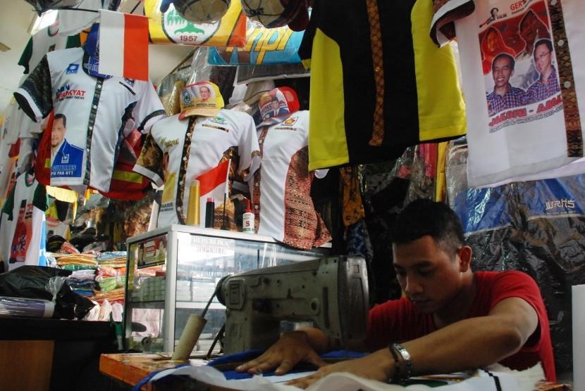 Pekerja menyelesaikan jahitan kaos bergambar calon gubernur DKI Jakarta di Pasar Senen, Jakarta, Senin (2/4). (Republika/Agung Fatma Putra)