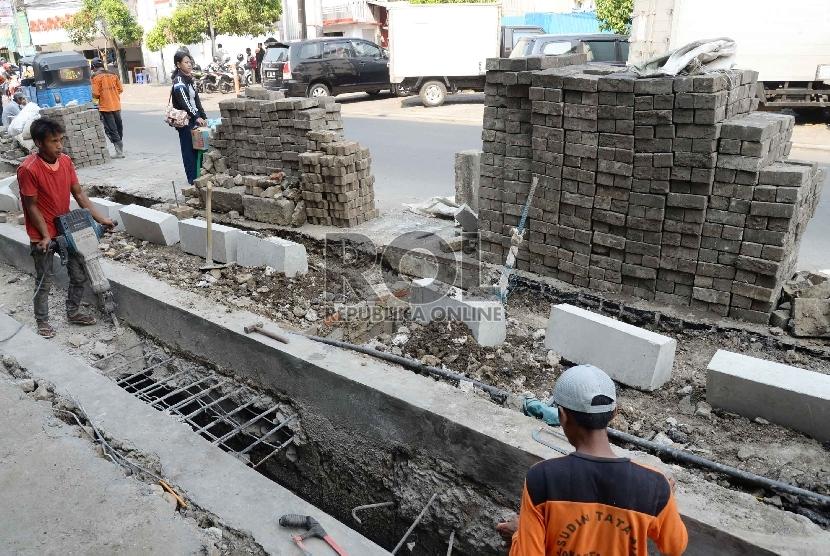 Pekerja menyelesaikan perbaikan saluran air di Jalan Sabang, Jakarta Pusat, Rabu (11/11).     (Republika/Yasin Habibi)
