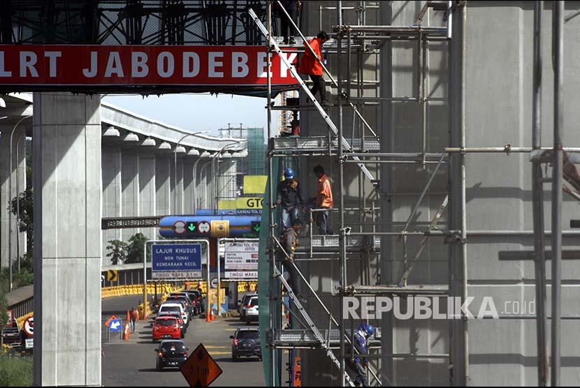 Pekerja menyelesaikan proyek pembangunan kereta ringan atau Light Rail Transit (LRT) di samping tol Jagorawi,  Cibubur, Jakarta Timur, Kamis (23/11).  Direktur Keuangan KAI Didiek Hartantyo mengatakan, pembengkakan nilai investasi pembangunan proyek LRT yang tadinya sebesar Rp26,7 triliun menjadi Rp31 triliun, masih belum final.