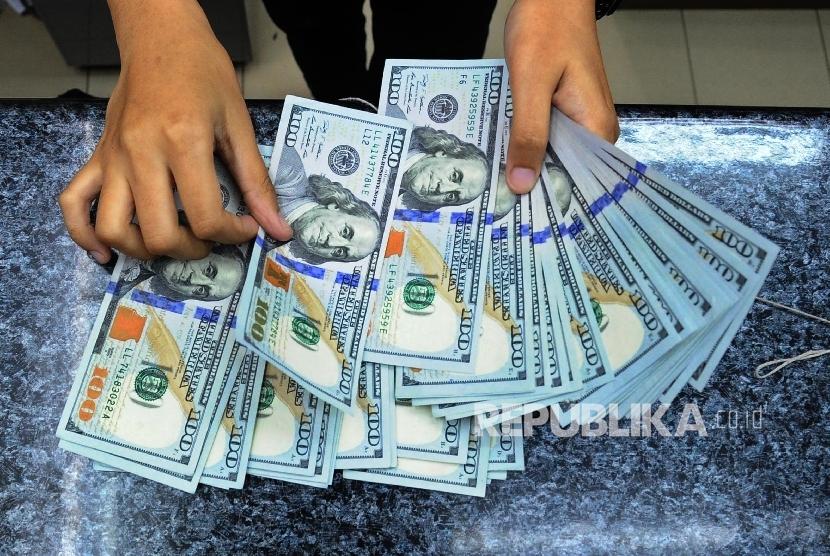 Pekerja sedang menghitung mata uang dolar di money change. ilustrasi