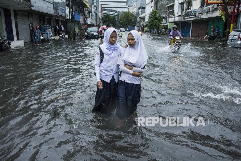 Pelajar berjalan melintasi air banjir di kawasan Sawah Besar, Jakarta, Selasa (21/2).