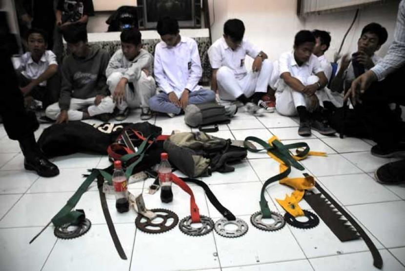 Pelajar yang terlibat tawuran ditahan petugas kepolisian beserta barang bukti. (Ilustrasi)