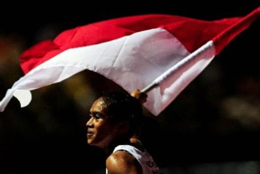 Pelari putri Indonesia Triyaningsih, melakukan selebrasi usai finis diurutan pertama pada pertandingan lari nomor 5000 meter, cabang Atletik Sea Games ke 26 di Stadion Atletik Jakabaring Sports City, Palembang, Sumatera Sealatan, Senin (14/11).