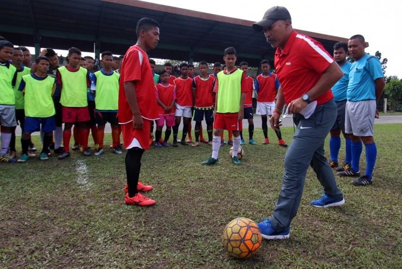 Pelatih Timnas U-16 Fachri Husaini (kanan) mengajarkan tehnik sepak bola kepada para peserta seleksi calon pemain Timnas U-16 Regional Sumatera di Stadion USU Medan, Sumatera Utara, Senin (13/3).