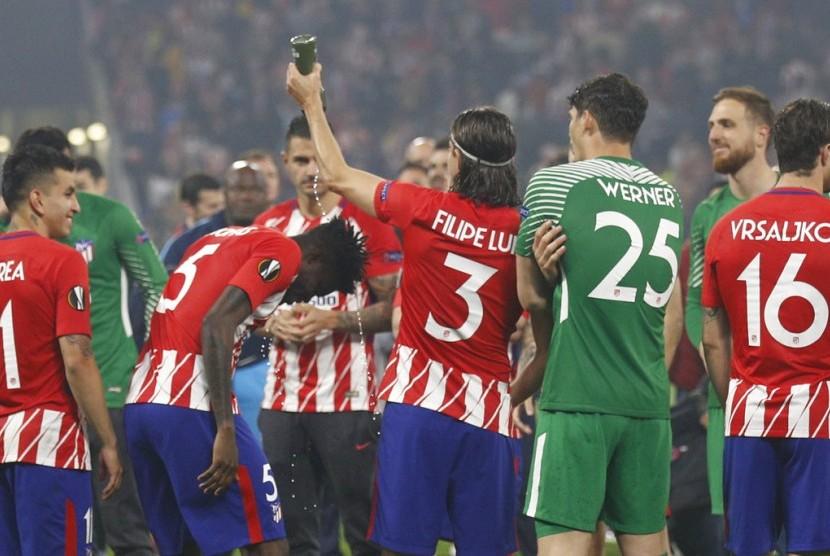 Pemain Atletico Filipe Luis menuang air ke rekannya Thomas Parter saat menunggu seremoni final Liga Eropa, Kamis (17/5). Dalam final Atletico keluar sebagai juara.