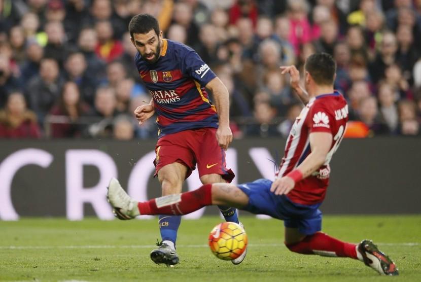 Pemain Barcelona Arda Turan dan pemain Atletico Madrid Jose Maria Gimenez dalam pertandingan, Sabtu (30/1), di Camp Nou.