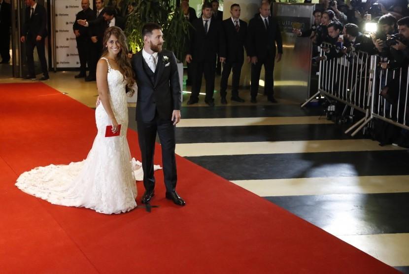 Pemain Barcelona, Lionel Messi (kanan), bersama istrinya, Antonella Roccuzzo (kiri), berpose di depan awak media usai menggelar acara pernikahan di Rosario, Santa Fe, Argentina, Jumat (30/6).